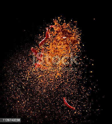 Cayenne pepper powder explosion isolated on black background,Flying Cayenne pepper,Motion blur