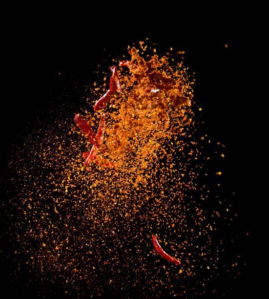 explosão de pó de pimenta caiena isolada no fundo preto, pimenta de caiena voando, motion blur - condimento temperos - fotografias e filmes do acervo