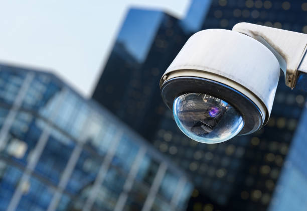 cctv security camera in a city with blury business building on background stock photo