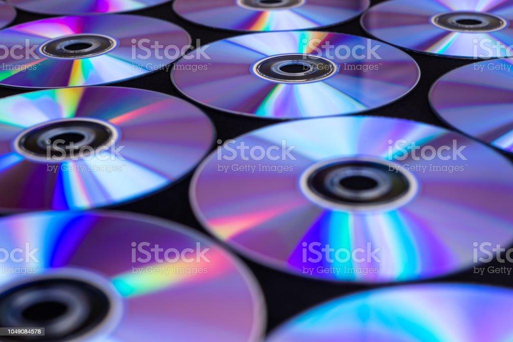 CDs / DVDs auf einem schwarzen Hintergrund liegend mit Reflexionen des Lichts. – Foto