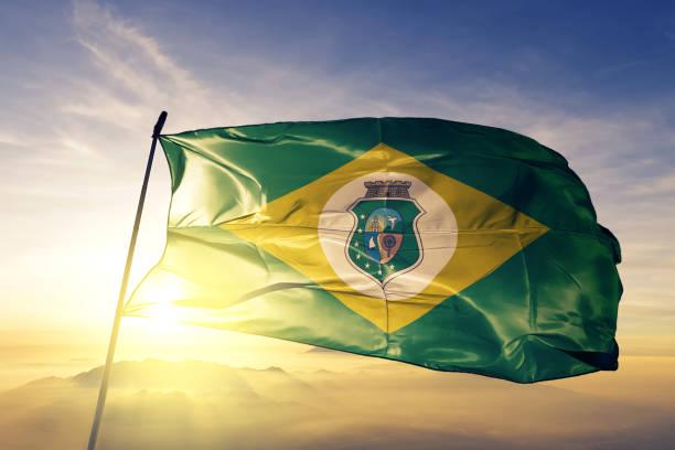 Ceara state of Brazil flag textile cloth fabric waving on the top sunrise mist fog stock photo