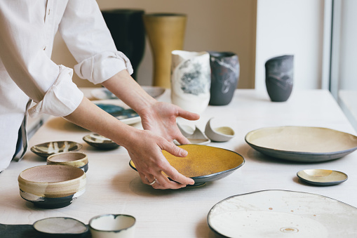 Hands of unrecognisable woman gallerist putting artisan's pots and dishware at shop window.