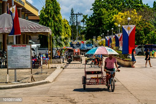 Cebu, Philippines - June 18, 2018: Cebu showing pedicab tricycle and two wheeled motorcycle on the street and pedestrians are walking with philippine flags inthe background in the Moalboal area with people on the background
