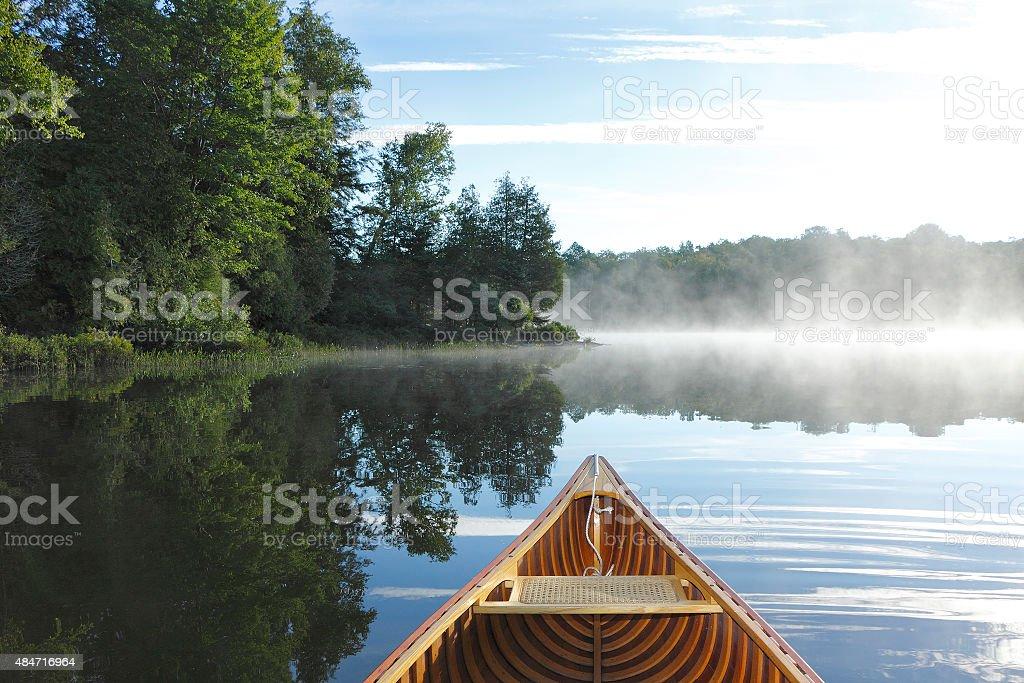 Cedar Canoe Bow on a Misty Lake stock photo