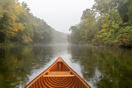 Cedar canoe on a river during a light rain