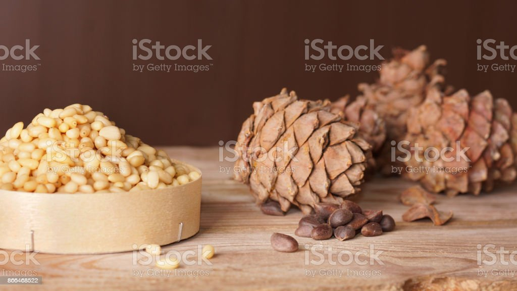 Cedar cones and pine nuts are on a wooden table stock photo