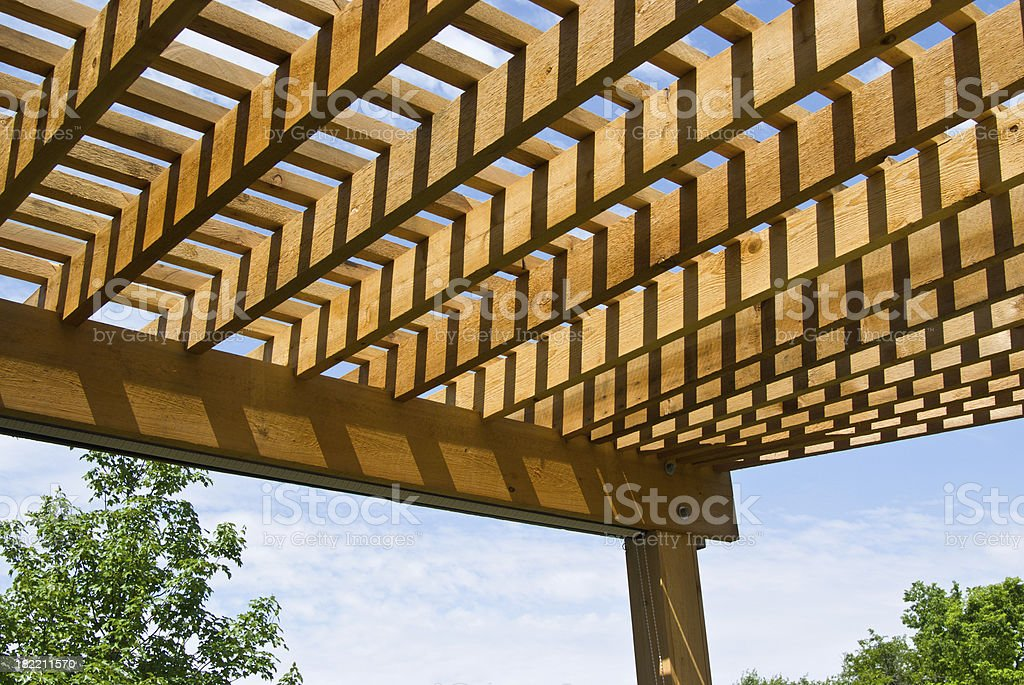 Cedar pergola with sky and trees in background stock photo