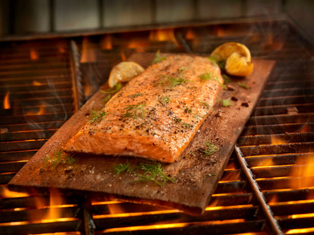 zedernholz plank lachs kochen auf dem grill - wärmeplatte stock-fotos und bilder