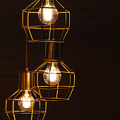 Ceiling chandelier with hanging three bulb lamps, yellow LED lighting elements covered with metal wire frame lampshades, square framed photo with selective focus