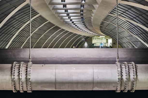 Deckenkonstruktion mit großen Rohrleitungen im Vordergrund. Innenaufnahme Moderne Architektur und Technik. U-Bahn Köln Heumarkt. – Foto
