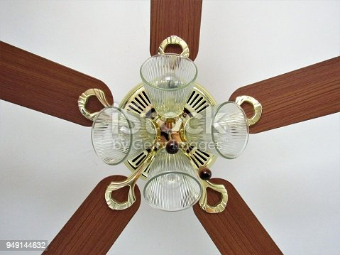 Shot of mounted ceiling fan, wooden blades, glass bulbs and brassy hardware