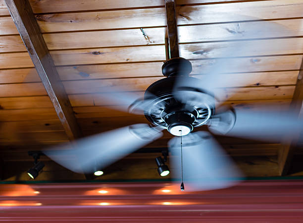 Ceiling Fan Spin A ceiling fan shows motion blur as its blades spin around. ceiling fan stock pictures, royalty-free photos & images