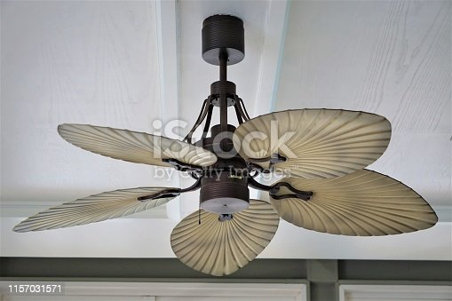 Ceiling fan with electric lamp decorated on white wooden background in the living room of a condominium.