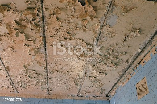 istock Ceiling in the destroyed building and crash. 1070591778