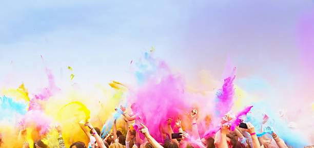 celebrants dancing during the color holi festival - multi colored stock pictures, royalty-free photos & images