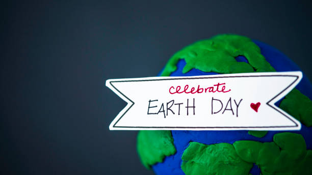 celebrate earth day. handmade globe with banner - earth day stock pictures, royalty-free photos & images