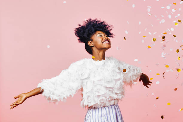 Celebrate happiness and joy- young girl throwing confetti Portrait of a young girl with a big smile throwing confetti in the air, isolated on pink studio background dress stock pictures, royalty-free photos & images