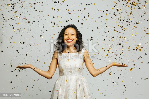Celebrate life, portrait of a smiling woman with arms out and golden confetti falling, isolated on gray studio background