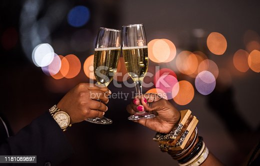 Closeup of two female hands toasting champagne glasses to celebrate a deal in evening