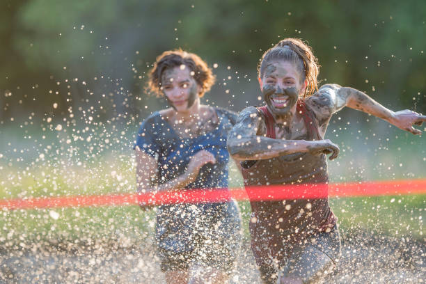 Celebrating a Win Beautiful blonde young woman leaping through the finish line in celebration while competing in a mud run for charity. mud run stock pictures, royalty-free photos & images
