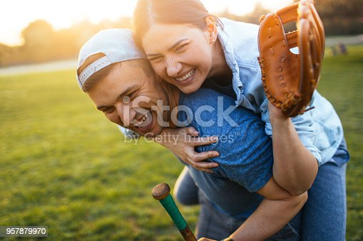 Young couple celebrating after a casual softball game