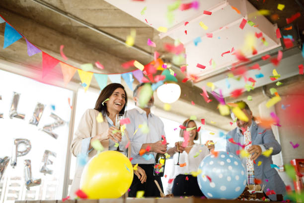 Celebrating birthday with confetti Coworkers celebrating birthday in office. anniversary stock pictures, royalty-free photos & images