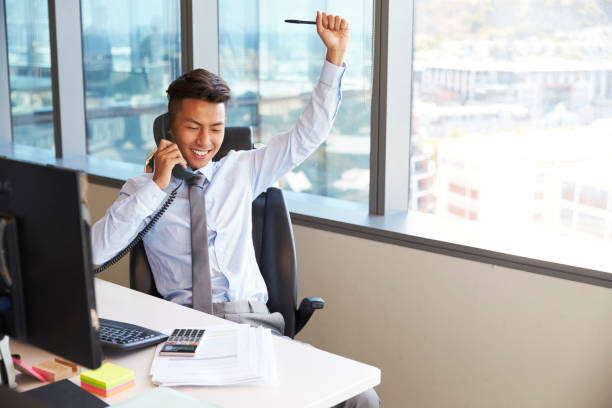 Celebrating Businessman Making Phone Call At Desk In Office stock photo