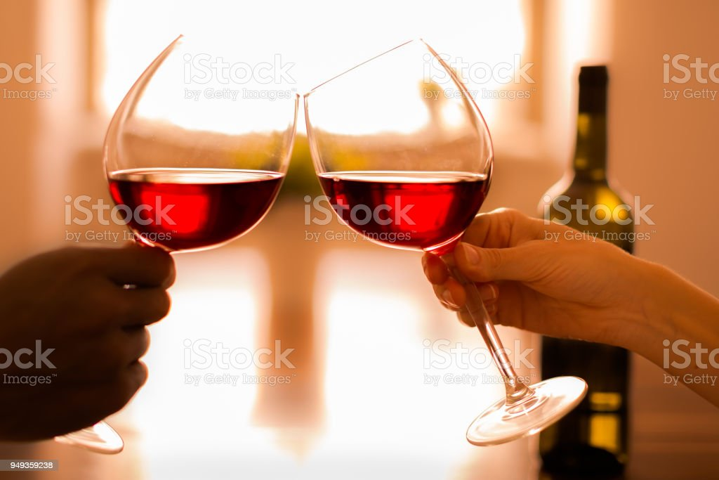 Celebrating by clinking glasses of red wine stock photo