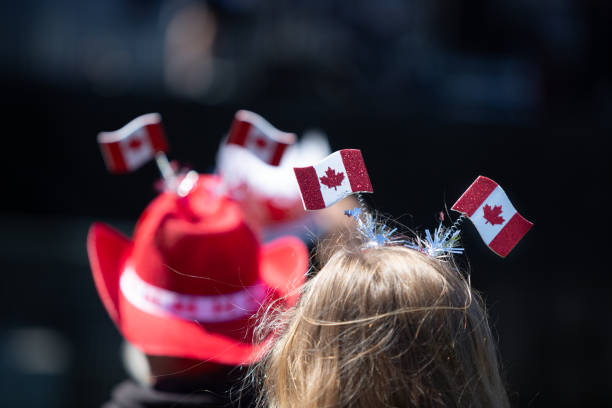 celebrating canada day with a headdress made of canada flags. - canada day stock pictures, royalty-free photos & images