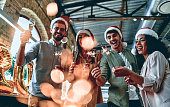 Merry Christmas and Happy New Year 2020!Multiracial young creative people are celebrating holiday in modern office. Group of young business people are drinking champagne with sparkling bengal lights in coworking. Successful hipster team of freelancers.