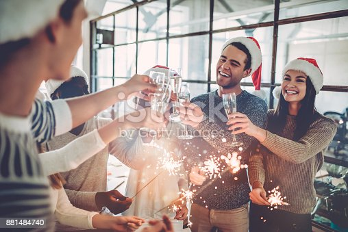Merry Christmas and Happy New Year 2018!Multiracial young creative people are celebrating holiday in modern office. Group of young business people are drinking champagne with sparkling bengal lights in coworking. Successful hipster team of freelancers.