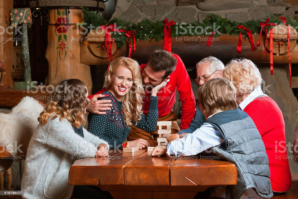 Celebrating Christmas Happy multi generation family: grandparents, parents and children sitting at the talbe and playing together. Fireplace in the background. Active Seniors Stock Photo
