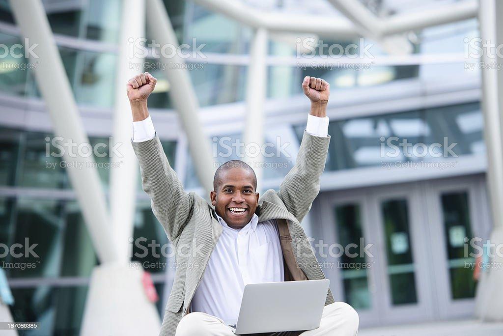 A happy African-American man sitting cross-legged on the floor. He...