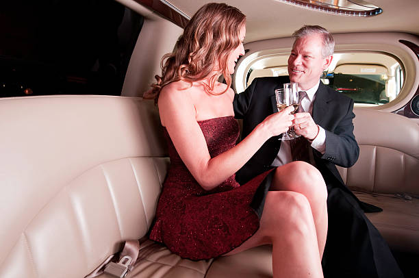 celebrating couple in limo with champagne glasses - middle aged man dating bildbanksfoton och bilder