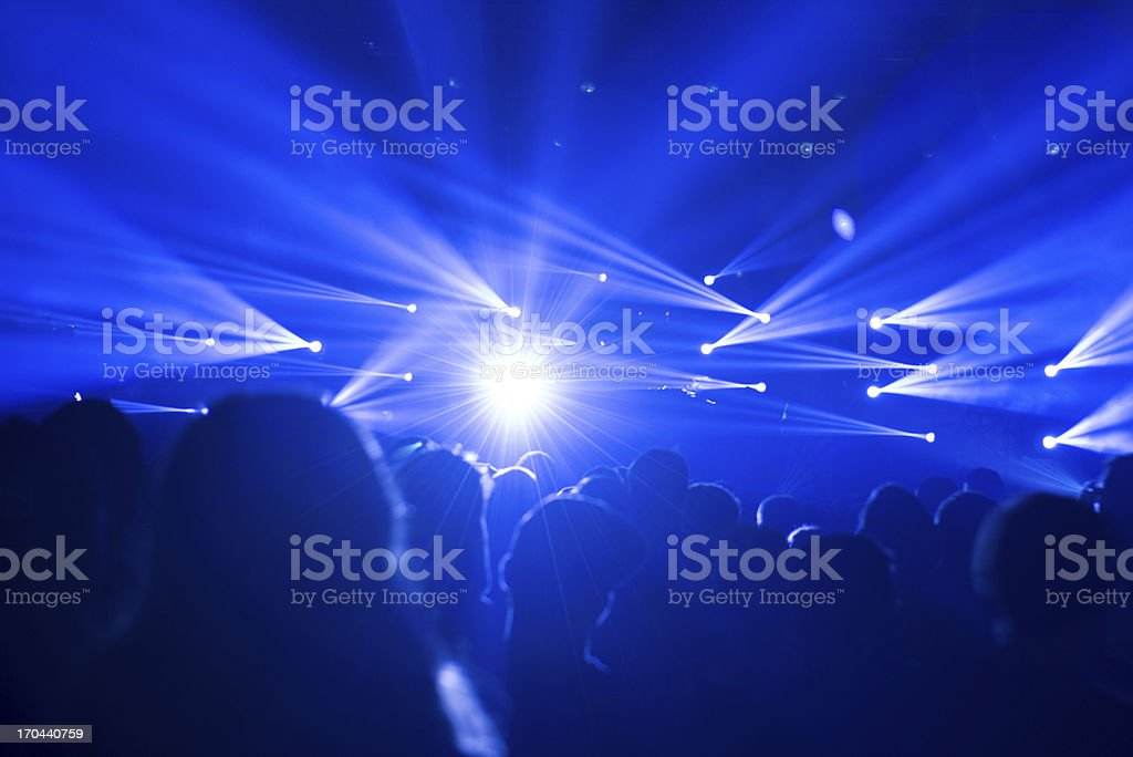 celebrating crowd with blue lights at a concert - festival royalty-free stock photo