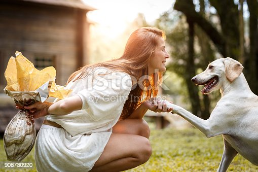 A woman celebrating easter with easter eggs and her dog.