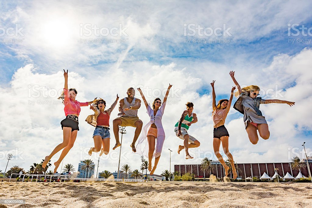 Celebrating Group of Friends Jumping at the Beach stock photo