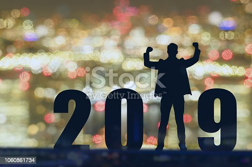 1042088340 istock photo celebrating new year 2019 Silhouette freedom young hope business man standing and enjoying on the the top of the building, city scape, landscape and 2019 years , copy space 1060861734