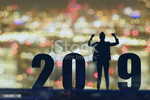 1042088340 istock photo celebrating new year 2019 Silhouette freedom young hope business man standing and enjoying on the the top of the building, city scape, landscape and 2019 years , copy space 1060861748