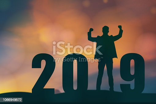 1042088340 istock photo celebrating new year 2019 Silhouette freedom young hope business man standing and enjoying on the the top of the building, city scape, landscape and 2019 years , copy space 1066949572