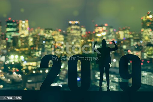 1042088340 istock photo celebrating new year 2019 Silhouette freedom young hope business man standing and enjoying on the the top of the building, city scape, landscape and 2019 years , copy space 1076012730