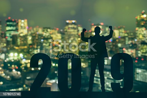1042088340 istock photo celebrating new year 2019 Silhouette freedom young hope business man standing and enjoying on the the top of the building, city scape, landscape and 2019 years , copy space 1076012740