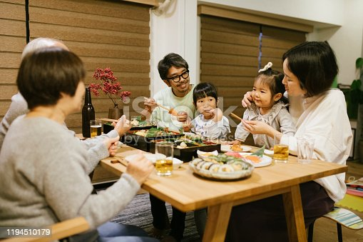 Three generation family celebrating on New Years eve. Osechi Ryori - a traditional Japanese food on the table.