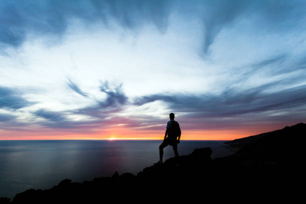 Celebrating or meditating man looking at sunset ocean Celebrating or meditating man looking at sunset ocean. Hiker with backpack on top of mountain looking at beautiful inspirational night landscape. one man only stock pictures, royalty-free photos & images
