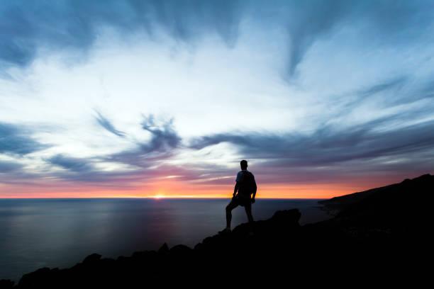 feiern oder meditieren mann blick auf sonnenuntergang ozean - ein mann allein stock-fotos und bilder