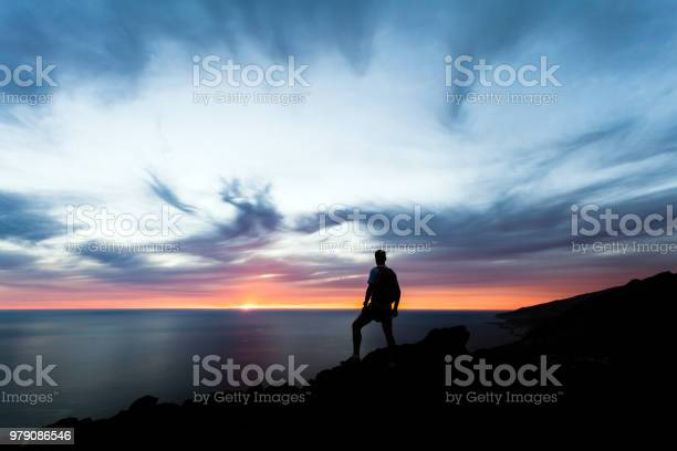 Photo of Celebrating or meditating man looking at sunset ocean