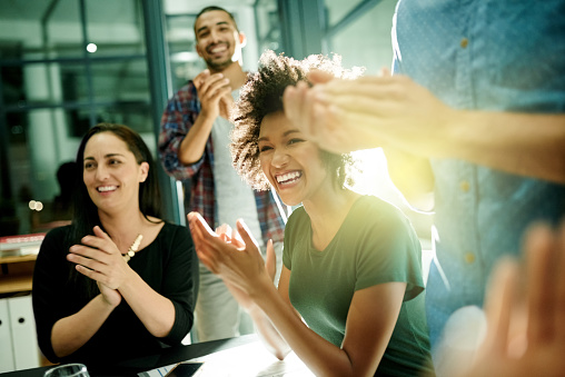 Shot of a team of creative businesspeople applauding an achievement  while working late in the boardroom