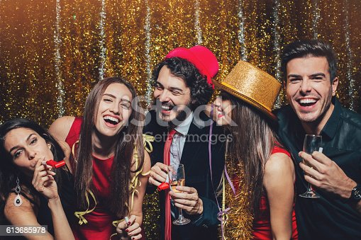 Group of young people in formal wear having fun and drinking champagne at a party.