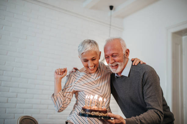 Celebrating special day together Mature couple celebrating holding a birthday cake 60 64 years stock pictures, royalty-free photos & images