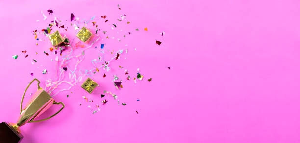 Celebrando el éxito que ha sucedido, trofeo de oro colocado sobre un fondo rosado. - foto de stock